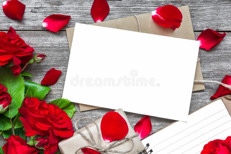 Пустая белая поздравительная открытка с букетом цветков красной розы и конверт с лепестками, выровнянной тетрадью и подарочной ко стоковые изображения