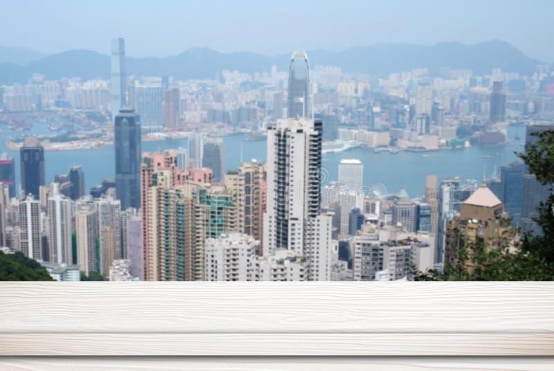 Пустая белая таблица над предпосылкой городского пейзажа нерезкости стоковое фото rf