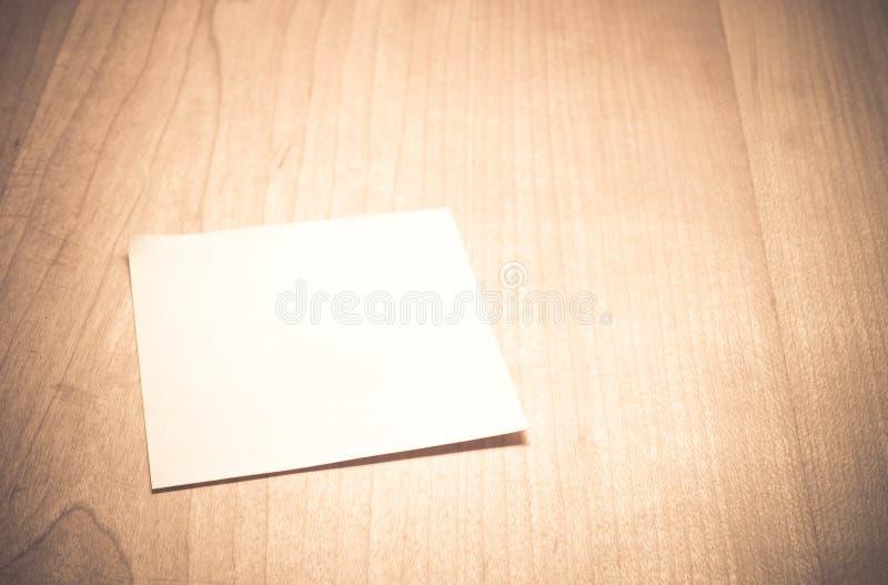 Пустая бумага примечания на деревянном столе с винтажным фильтром стоковое изображение