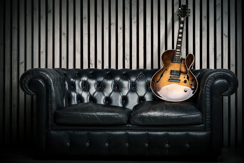 Пустая винтажная софа и электрическая гитара с современной деревянной предпосылкой студии звукозаписи стены Концепция музыки с ни стоковое фото