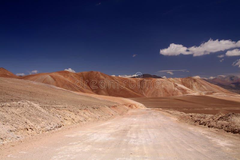 Пустая грязная улица к красочным горам Copiapo в пустыне Atacama, Чили стоковые фотографии rf