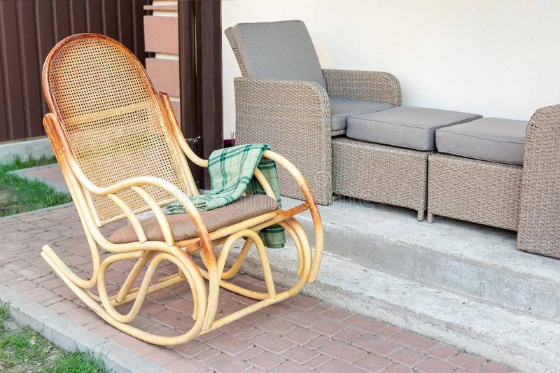 Пустая деревянная кресло-качалка ротанга с зеленой шотландкой фланели на задворк террасы дома outdoors Мирный экстерьер дома обра стоковое изображение rf