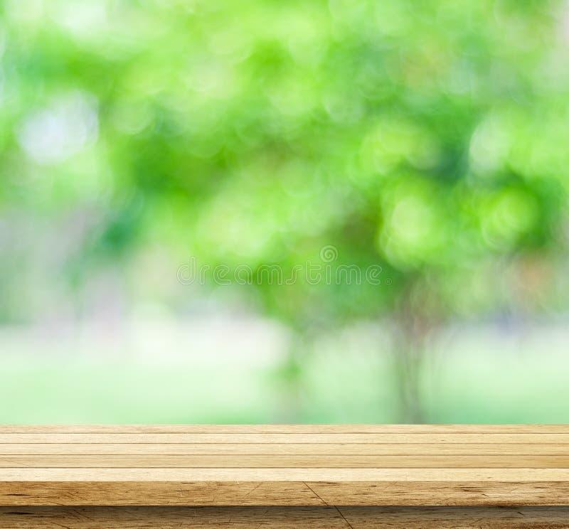 Пустая деревянная таблица над запачканными деревьями с предпосылкой bokeh стоковая фотография rf