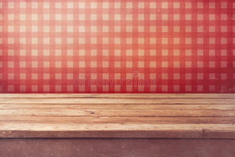 Пустая деревянная таблица палубы над проверенными красными обоями Винтажный интерьер кухни стоковые фото