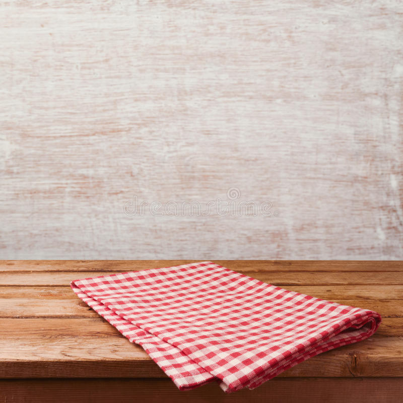 Пустая деревянная таблица палубы с красным цветом проверила скатерть над деревенской предпосылкой стены для дисплея монтажа проду стоковые изображения