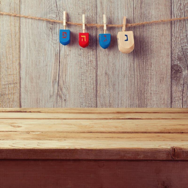 Пустая деревянная таблица палубы с смертной казнью через повешение закручивая верхней части dreidel Хануки на строке стоковые фото