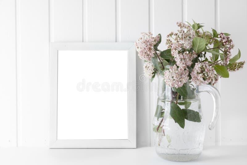 Пустая картинная рамка, украшенная с букетом розовой естественной подачи стоковое фото rf