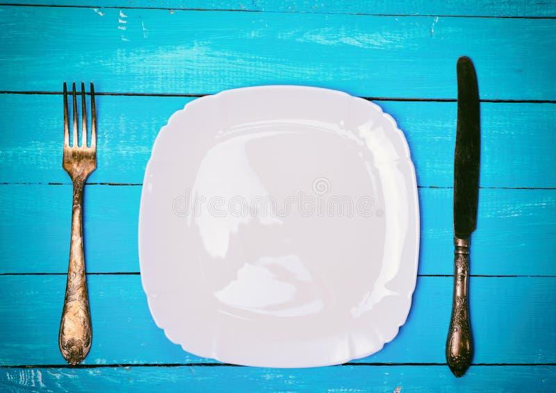 Пустая квадратная белая плита с железной вилкой и ножом стоковое изображение rf