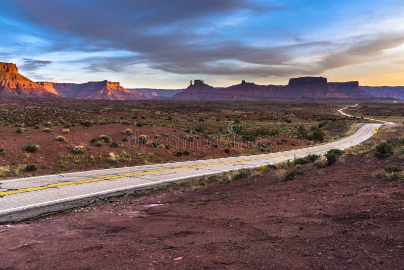 Пустая дорога водя к Moab Юте на замке Valle трассы 128 захода солнца стоковые фотографии rf