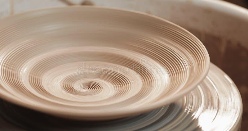 Пустая плита со сбросом вращает на колесе гончарни, конце вверх Обматывая структура глины Handmade, ремесло Белая глина стоковое фото rf