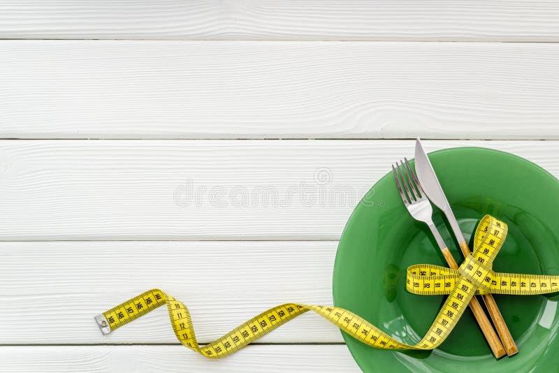 Пустая плита с вилкой и нож около измеряя ленты на белом деревянном космосе экземпляра взгляда сверху предпосылки стоковое фото