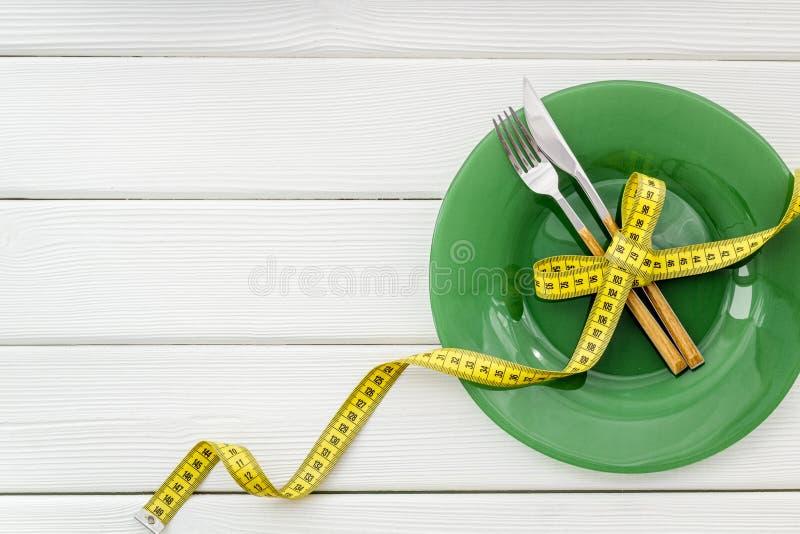 Пустая плита с вилкой и нож около измеряя ленты на белом деревянном космосе экземпляра взгляда сверху предпосылки стоковая фотография