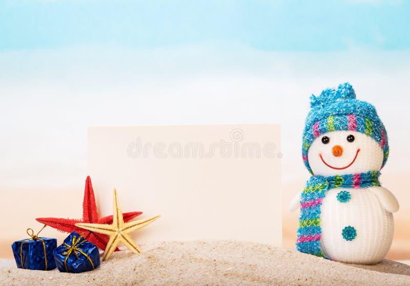 Пустая поздравительная открытка, морская звёзда, снеговик, подарки в песке моря стоковые изображения rf
