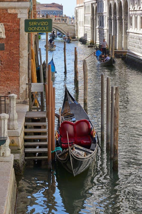 Пустая причаленная гондола и гондолы с людьми и туристами в солнечном дне в Италии стоковая фотография rf