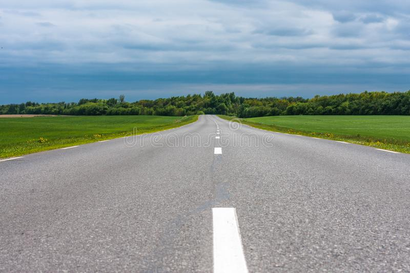 Пустая проселочная дорога асфальта с полями зеленой травы под бурными облаками в лете стоковые фото