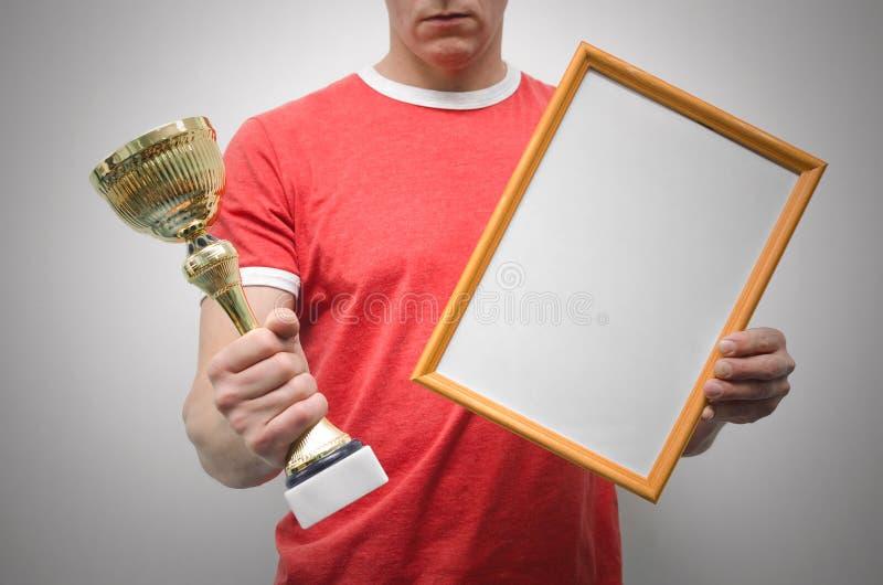 Пустая рамка диплома и золотая чашка награды в руках победителя стоковые фото