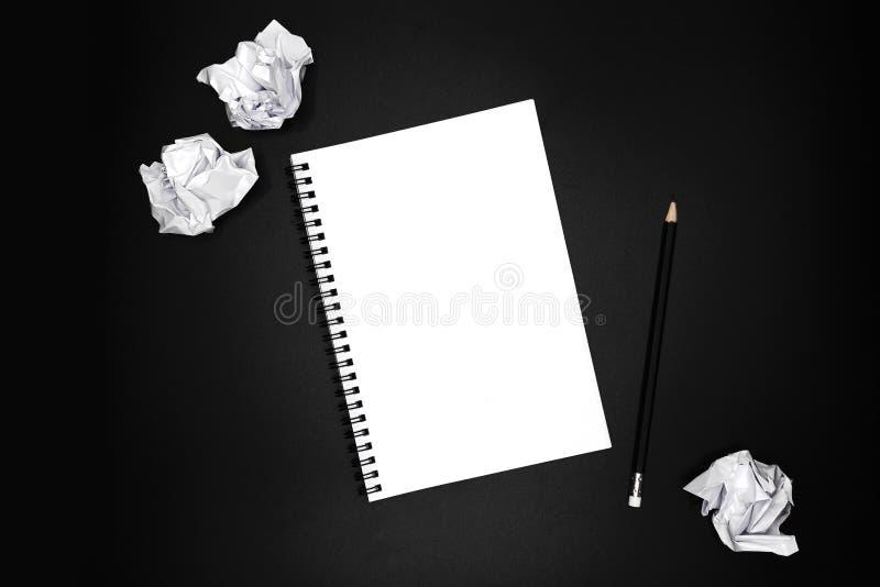 Пустая спиральная тетрадь с черным карандашем и скомканными бумагами на черной предпосылке стоковые фото