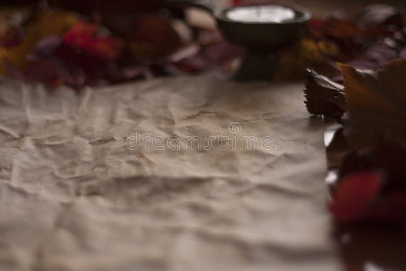 Пустая старая бумага с свечой и листьями на деревянном столе стоковое изображение rf