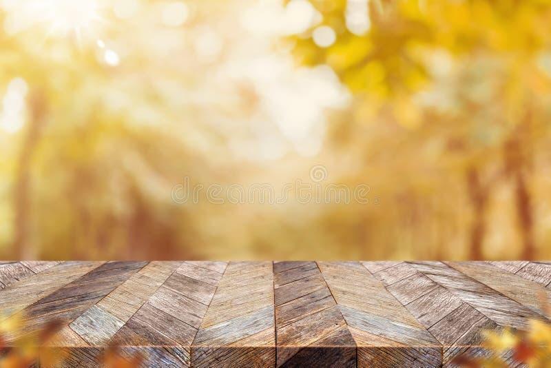 Пустая старая деревенская деревянная столешница планки с лесным деревом нерезкости с backgorund солнечного света, падения осени,  стоковое изображение rf