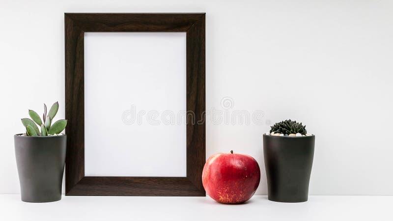 Пустая темная рамка фото, 2 succulents в темных баках и красного сочного яблоко на белой предпосылке Скандинавский стиль в стоковое изображение