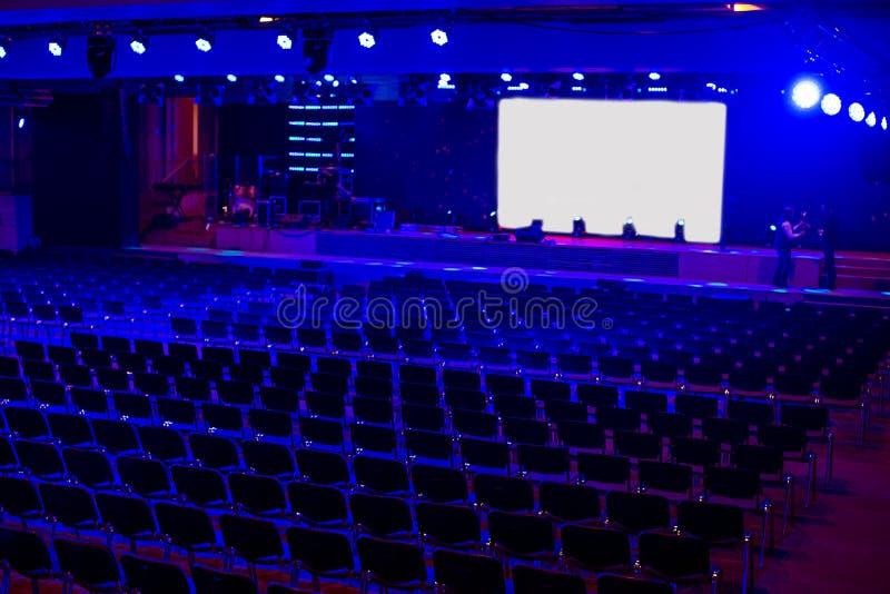 Пустая темная современная зала для событий и представления с белым экраном проекции и голубым светом Preperation для церемонии в  стоковые фото