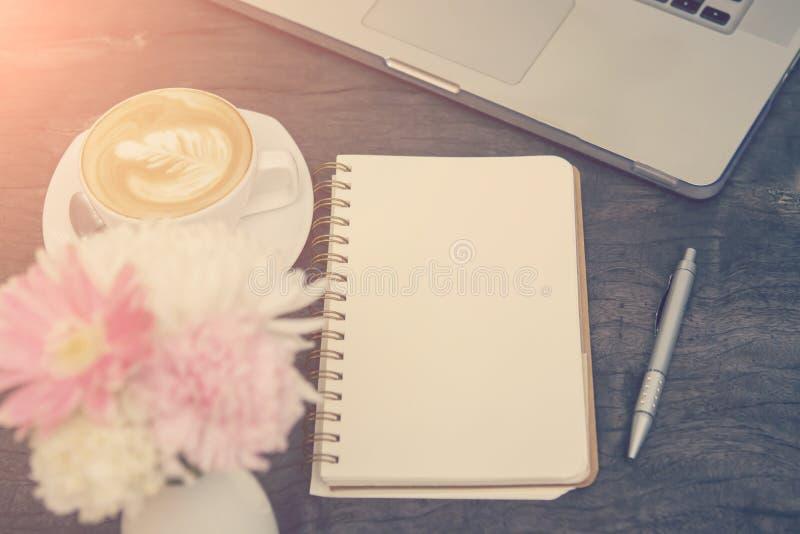 Пустая тетрадь с компьтер-книжкой и ручка на деревянной таблице стоковая фотография rf
