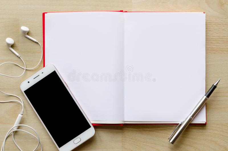 Пустая тетрадь с ручкой на деревянной таблице и зоне входного сигнала текста телефона шлемофона наручных часов современной стоковое изображение