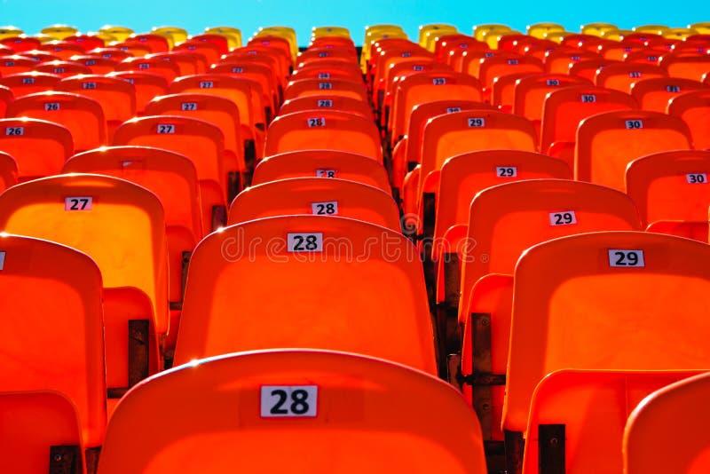 Пустая трибуна для вентиляторов на солнечный день сочетание из оранжевое и голубое стоковые фото