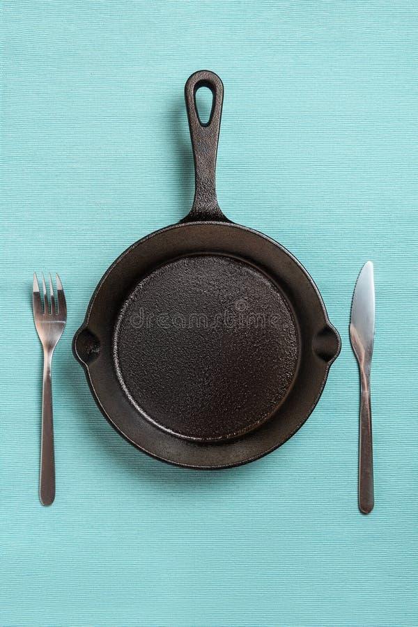 Пустая черная сковорода, вилка, нож, на скатерти бирюзы стоковая фотография rf