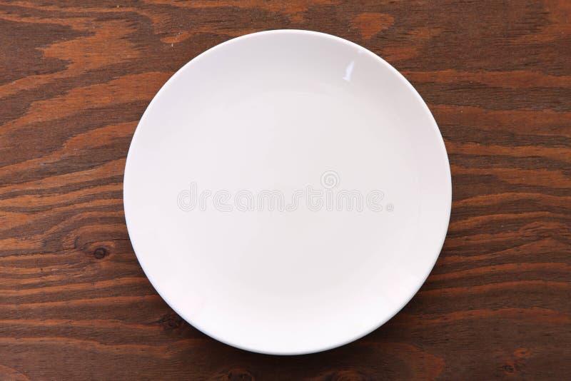 Пустое белое блюдо на коричневой таблице стоковое изображение