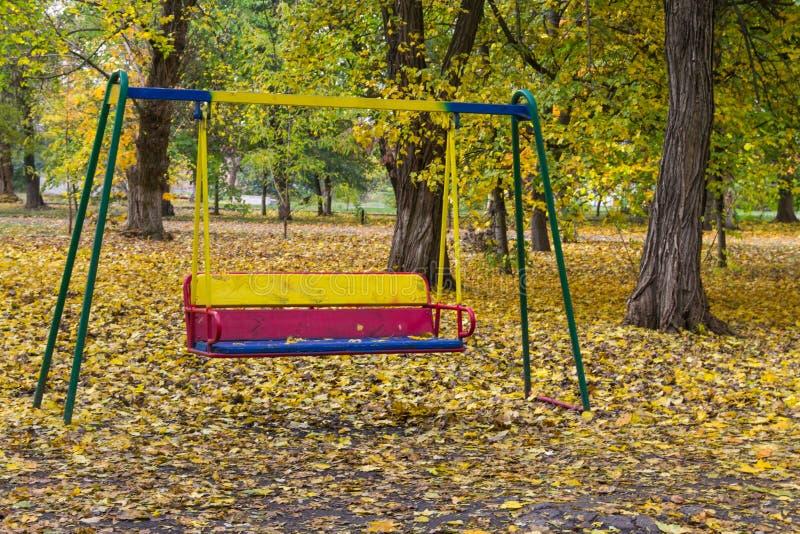 Пустое качание ` s детей в парке города стоковая фотография rf