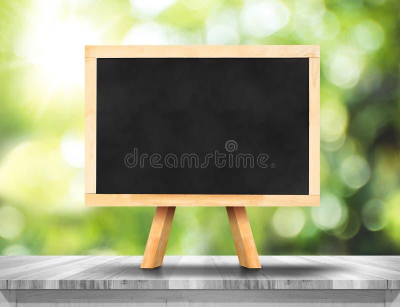 Пустое классн классный на белой деревянной таблице с tre солнца и нерезкости зеленым стоковое фото rf