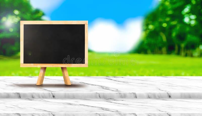 Пустое классн классный на белой мраморной столешнице с полем травы нерезкости стоковые фото