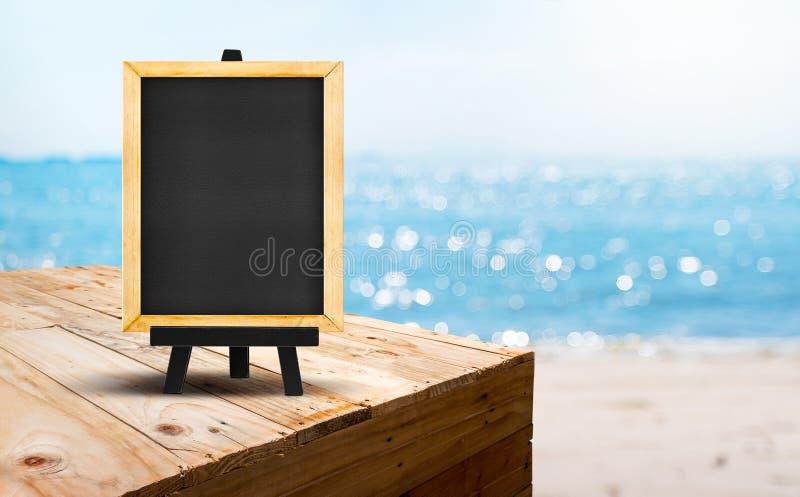 Пустое классн классный на деревянной стойке еды таблицы с пляжем a песка нерезкости стоковые фото