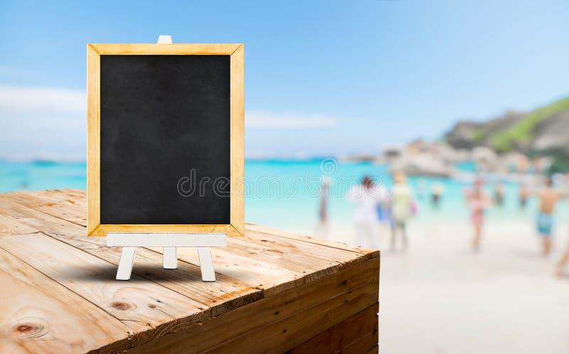 Пустое классн классный на деревянной стойке еды таблицы с пляжем a песка нерезкости стоковое изображение
