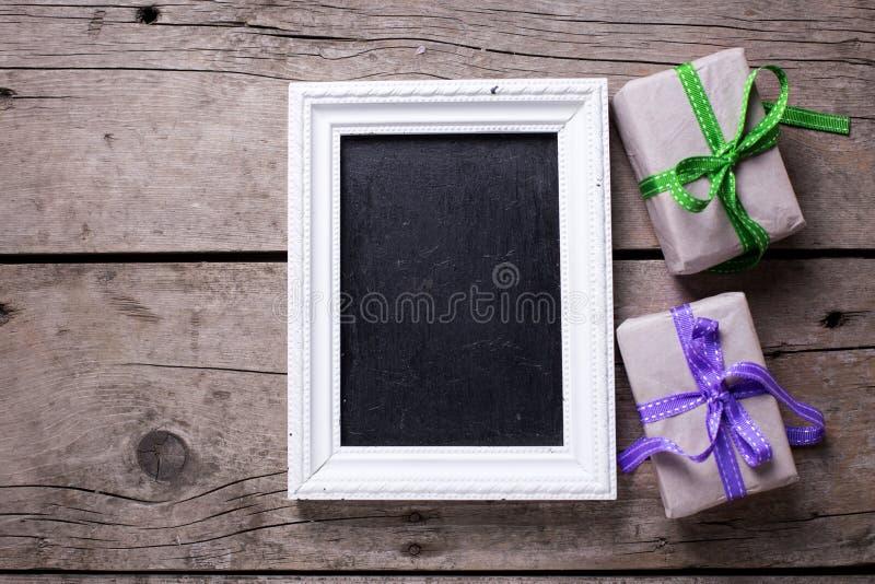 Пустое классн классный и праздничные подарочные коробки с настоящими моментами на постаретый стоковая фотография rf