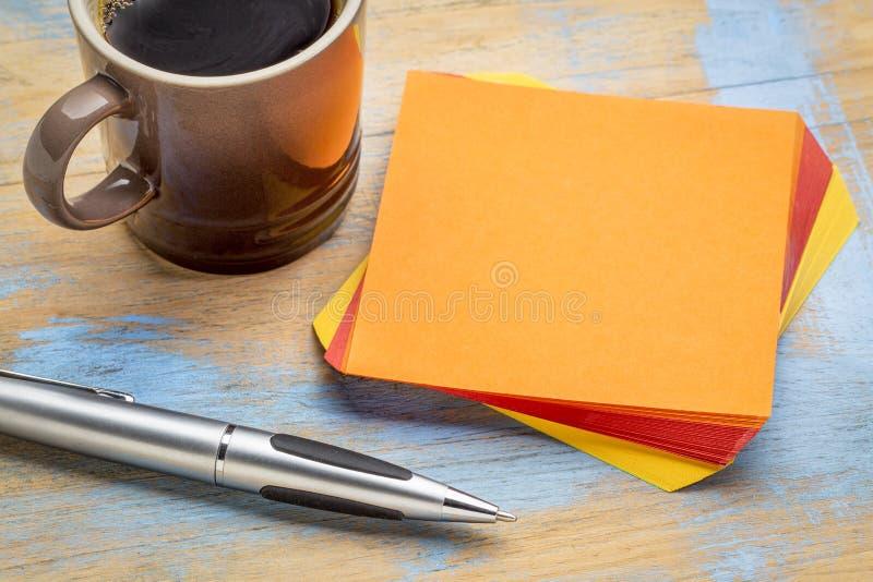 Пустое оранжевое липкое примечание с кофе стоковое изображение