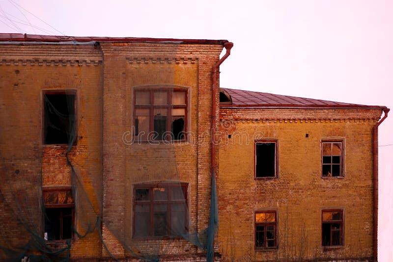 Пустое разрушенное здание со сломленными окнами розовый заход солнца неба Фото в красных цветах Утеснительная атмосфера разрушени стоковые фото