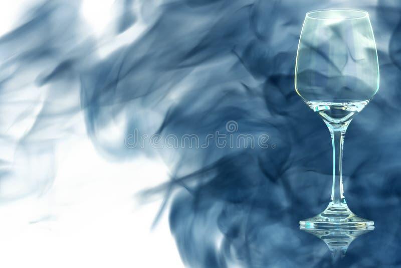 Пустое стекло красного вина охваченное в голубом дыме стоковое фото