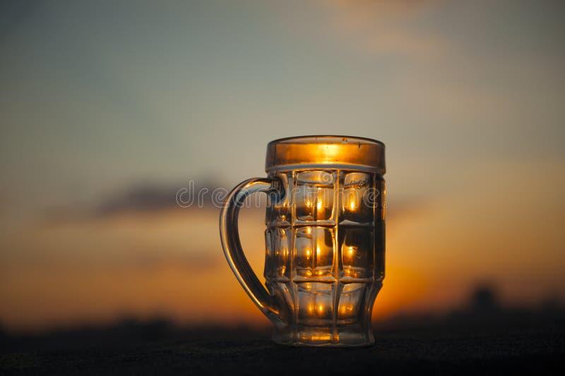 Пустое стекло пива на заходе солнца стоковое фото rf