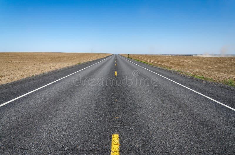 Пустое шоссе с трактором фермы в полях стоковые изображения