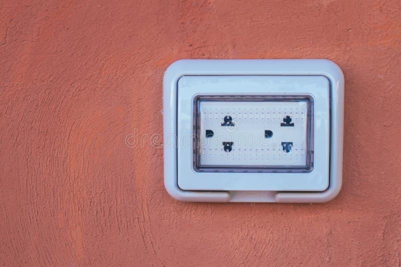 Пустой белый двойной электрический выход с пластиковой водоустойчивой установкой на коричневой стене глины стоковое изображение rf