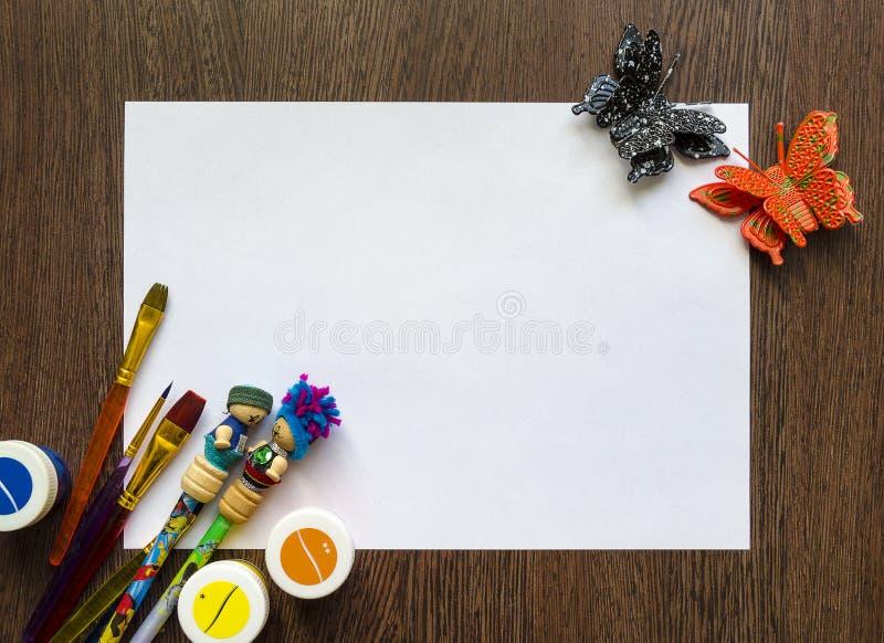 Пустой белый лист бумаги для вашего текста Покрашенные карандаши, ручки, краски вокруг его Модель-макет стоковое изображение rf