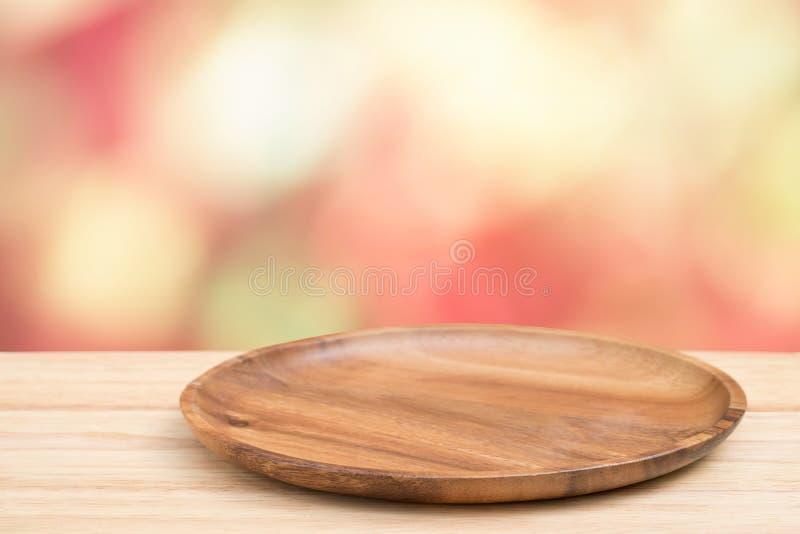 Пустой деревянный поднос на деревянном столе перспективы на верхней части над предпосылкой нерезкости Может быть используемое нас стоковое изображение rf