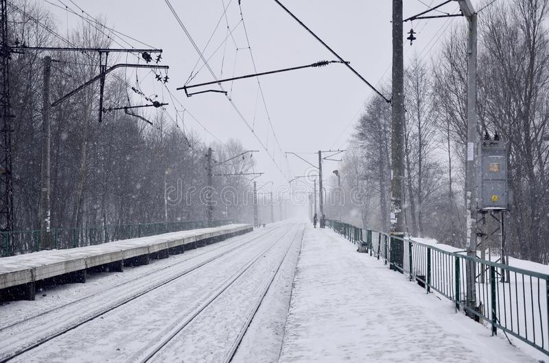Пустой железнодорожный вокзал в сильном снегопаде с сильным туманом Железнодорожные рельсы идут прочь в белый туман снега Концепц стоковая фотография rf