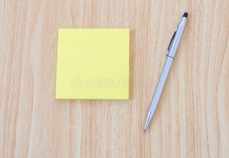 Пустой желтый блокнот с ручкой на деревянном столе офиса стоковые изображения rf