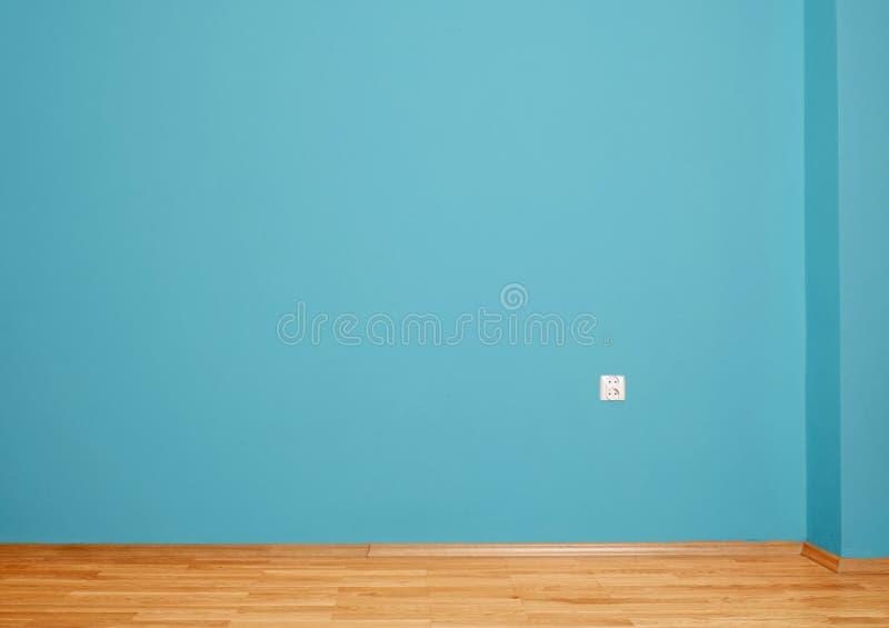 Пустой интерьер с деревянным полом, затыкает внутри стену и голубую стену стоковые фото