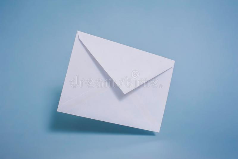 Пустой конверт белой бумаги на голубой предпосылке стоковые изображения