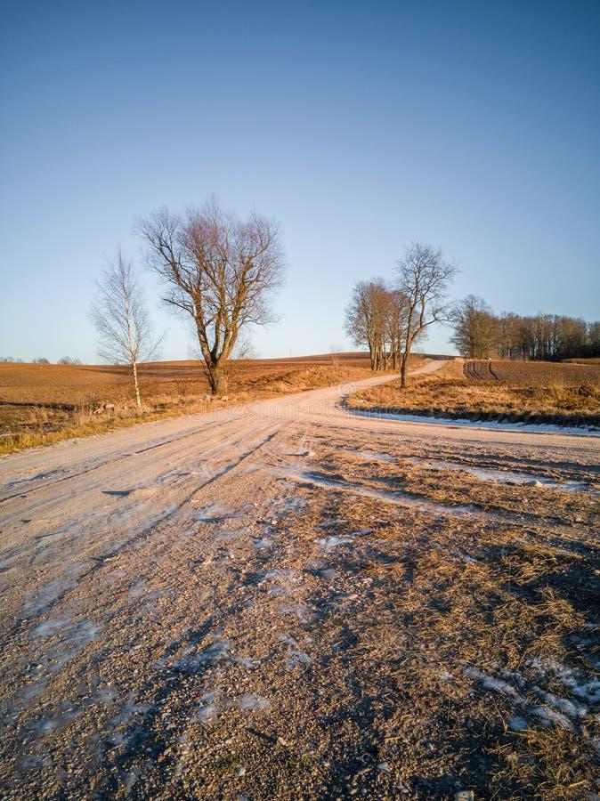 Пустой ландшафт сельской местности в солнечном зимнем дне со снегом отчасти покрывая землю, дорогу в середине фото - концепции  стоковая фотография rf