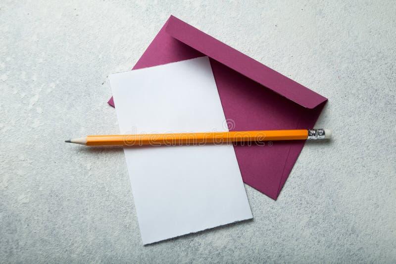 Пустой лист бумаги и конверт с карандашем на белом винтажном столе стоковые фотографии rf